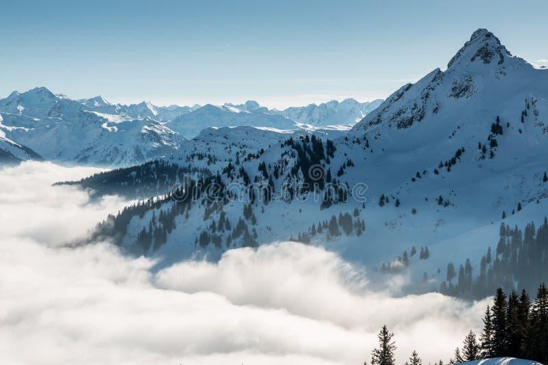 Neve na parte superior das montanhas e da névoa abaixo do vale imagem de stock