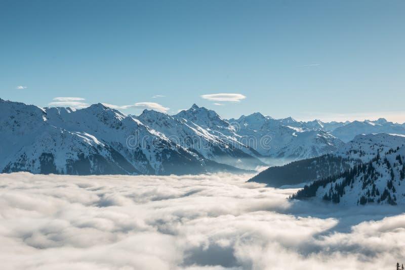 Neve na parte superior das montanhas e da névoa abaixo do vale imagens de stock