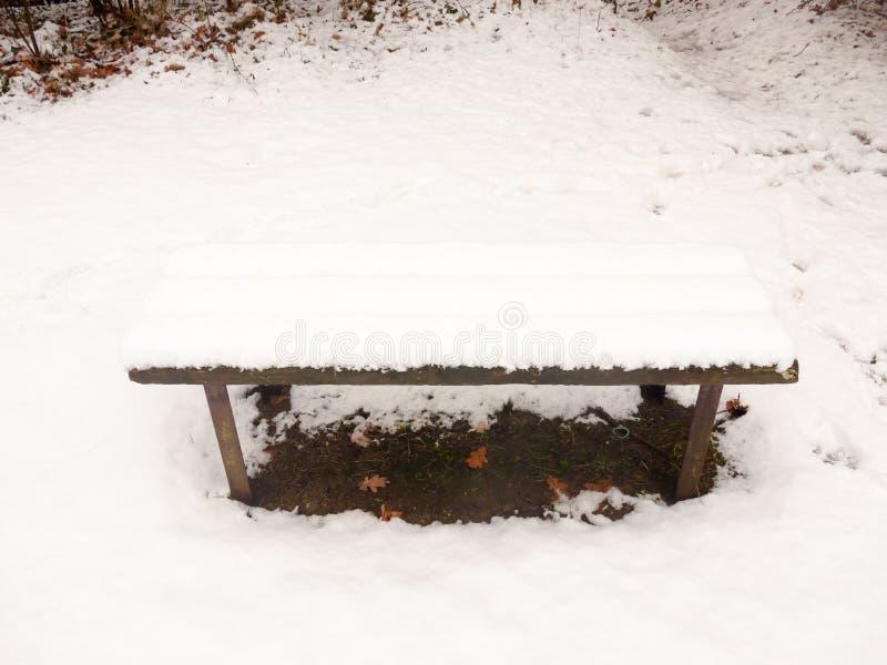 a neve pública coberta de madeira do banco fora da grama do inverno cobriu o wh imagem de stock royalty free