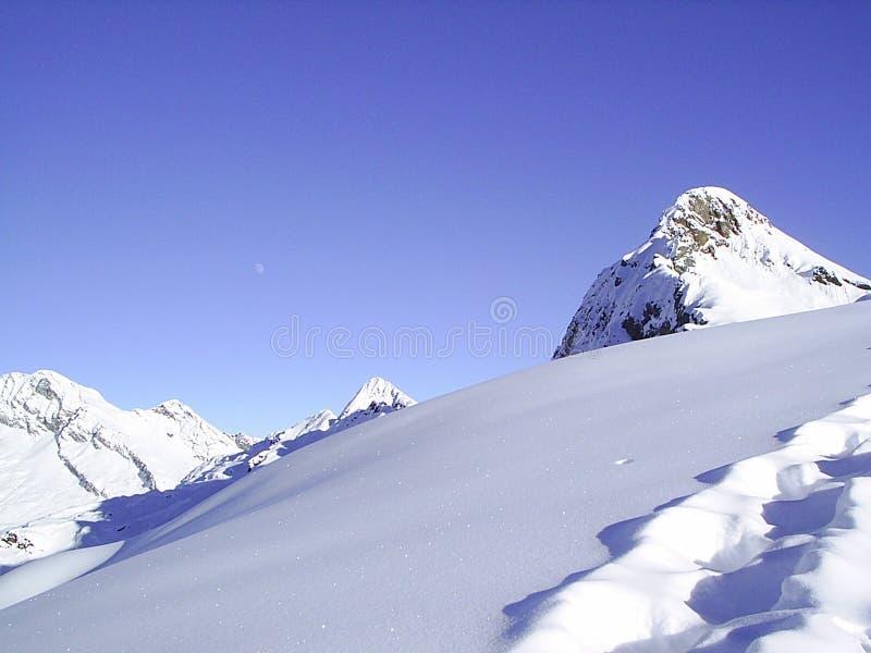 Neve, picchi e luna fotografie stock