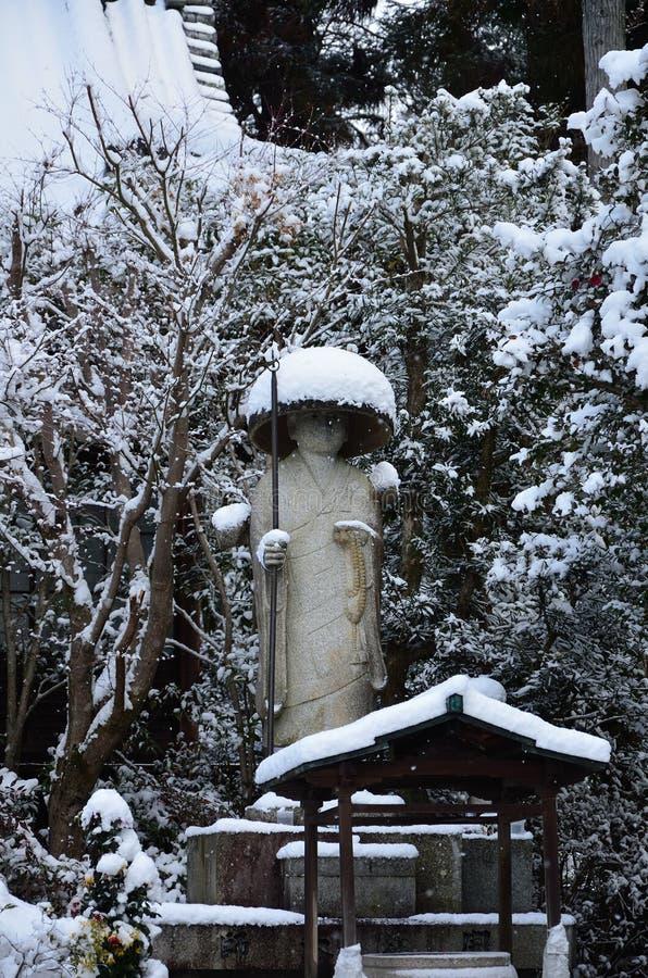 Neve que cai na Buda no jardim do templo, Kyoto Japão foto de stock