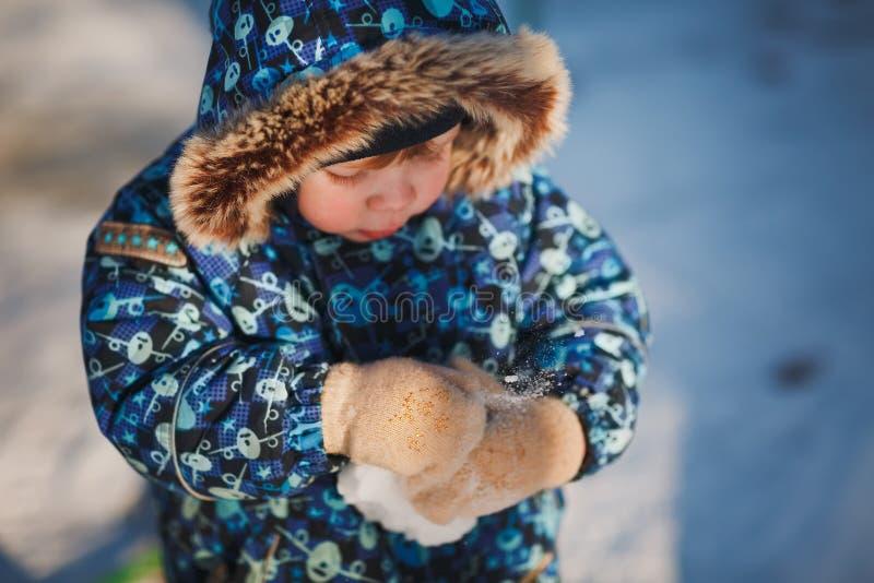 Neve quebradiço nas mãos de um rapaz pequeno em um revestimento azul do inverno com uma capa A neve no fundo Um dia de inverno en foto de stock
