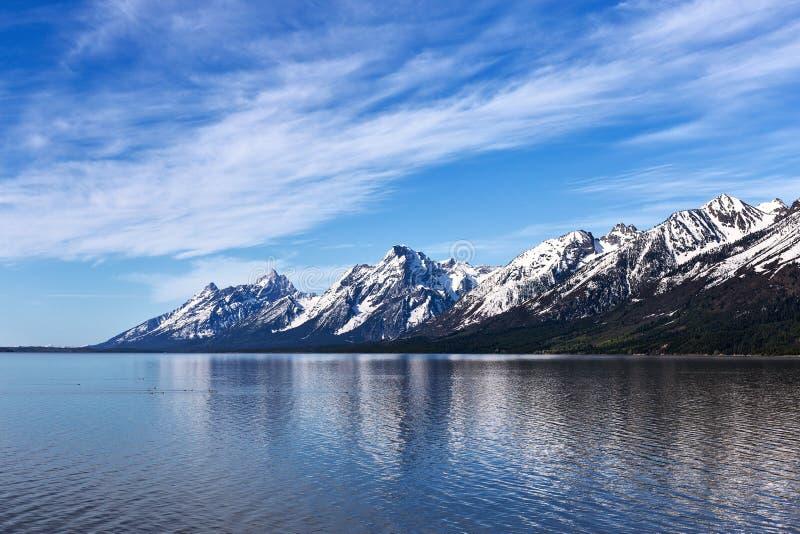 A neve refletindo de Jackson Lake tampou montanhas no parque nacional grande de Teton, Wyoming, EUA fotos de stock royalty free