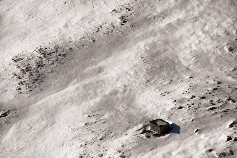 Neve sulle montagne e su una piccola cabina fotografia stock
