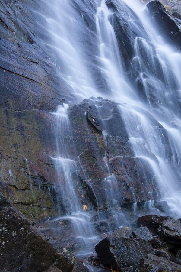 Nevelig water die over rotsen draperen stock foto