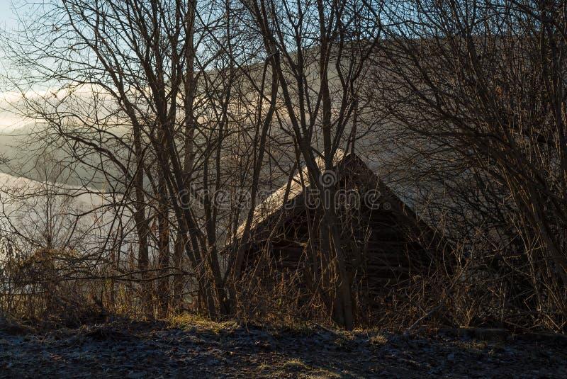 Nevelige en atmosferische ochtend met zonsopgang over meer, berg en een mysticus weinig plattelandshuisje in de wildernis met naa stock foto