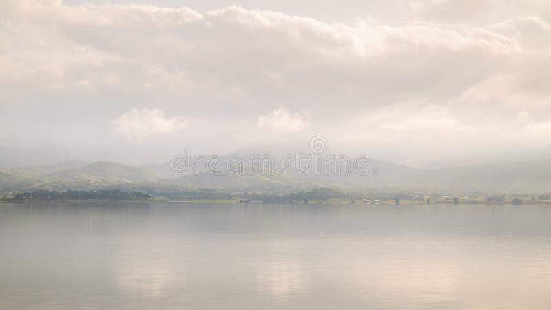 Nevelige ochtend van meer en bergketen stock afbeeldingen