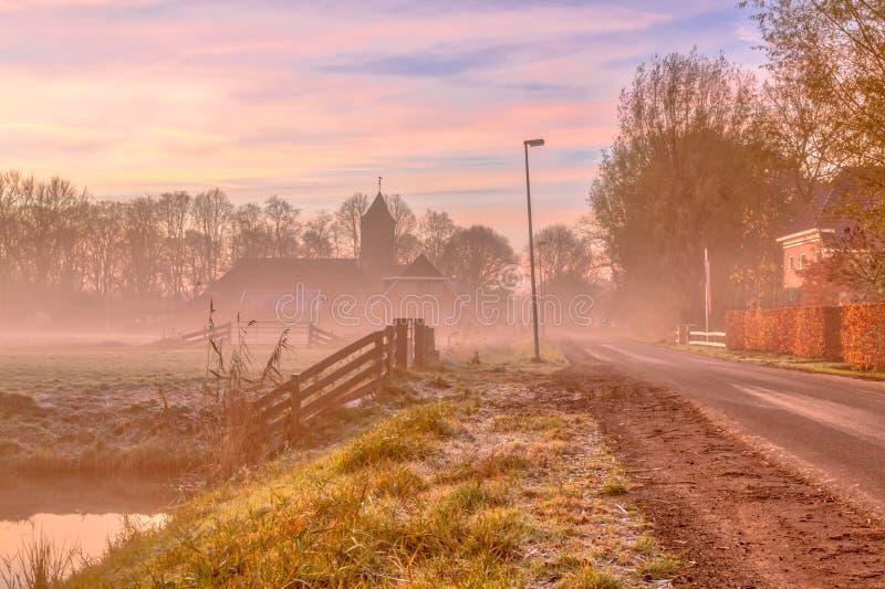 Nevelige straat in Nederlands dorp stock afbeelding