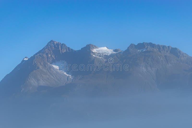 Nevelige verduisterde mening van sneeuw behandelde berg stock foto's