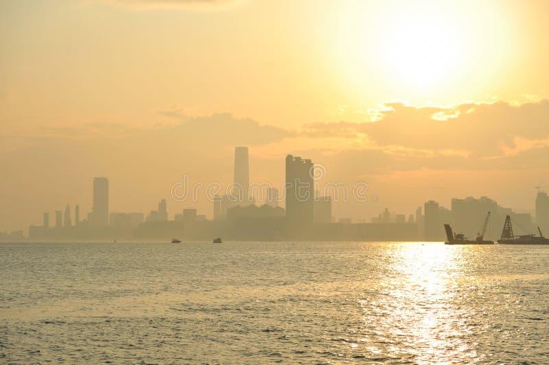 Nevelige zonsondergang in Kowloon, Hong Kong stock foto's