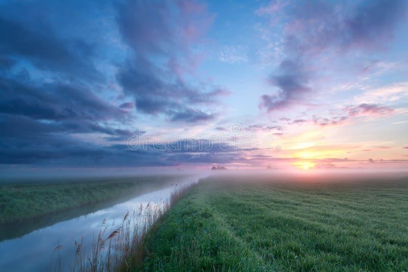 Nevelige zonsopgang over weide en rivier royalty-vrije stock fotografie