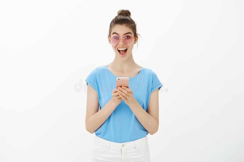 Never been so happy receiving message. Happy young woman in stylish sunglasses, smiling broadly and gazing joyfully at royalty free stock images
