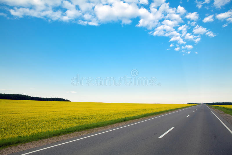 Never ending highway through green fields and blue stock photo