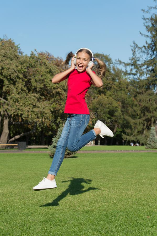 Never ending joy. Girl listening music modern gadget. Kid happy with wireless headset dancing running jumping. Stereo stock image