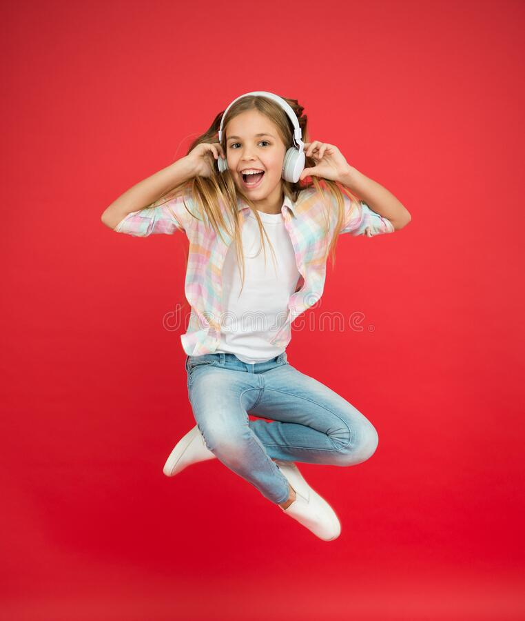Never ending joy. I believe i can fly. Girl listening music modern gadget. Kid happy with wireless headset dancing. Jumping. Stereo headphones. Kid using modern stock image