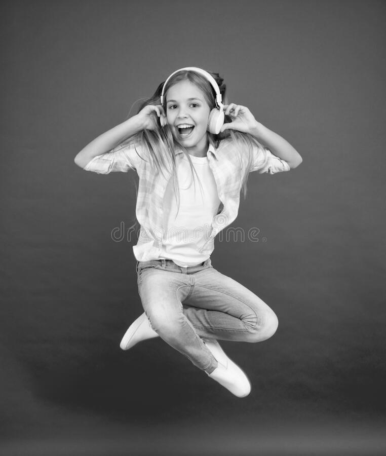 Never ending joy. I believe i can fly. Girl listening music modern gadget. Kid happy with wireless headset dancing. Jumping. Stereo headphones. Kid using modern royalty free stock image