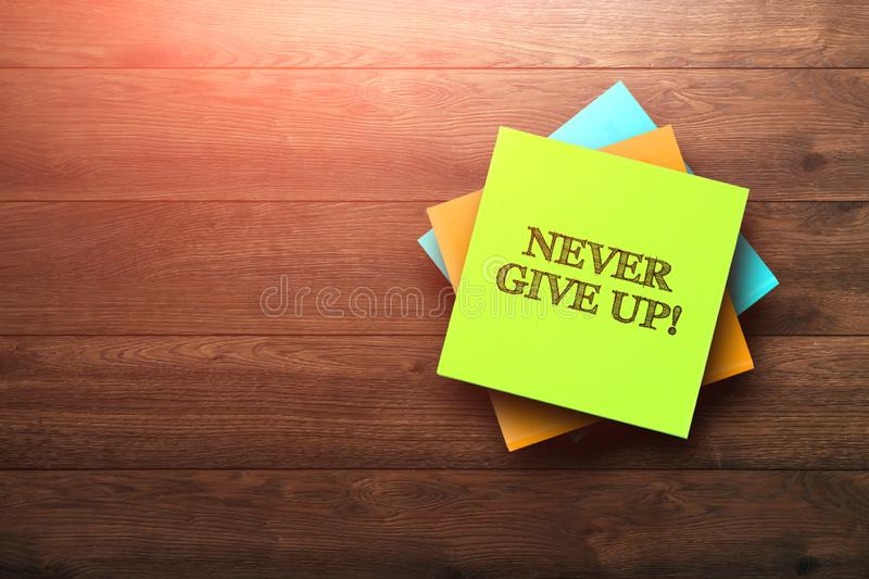 Never Give Up , the phrase is written on multi-colored stickers, on a brown wooden background. environment concept, strategy, plan royalty free stock image