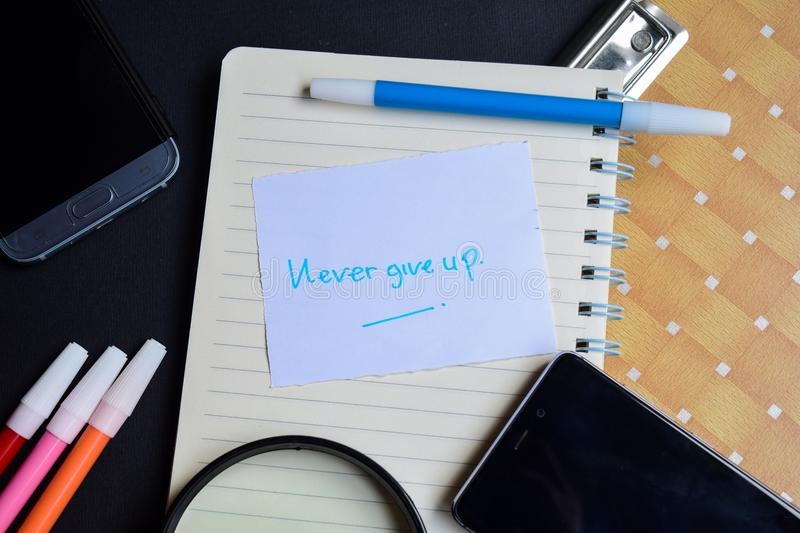 Never Give up word written on paper. Never Give up text on workbook, technology business concept royalty free stock photography