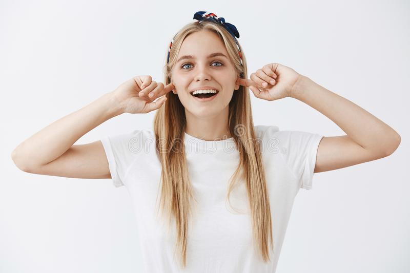 Never listen to haters and enjoy life. Portrait of good-looking happy and carefree blonde girl in headband and white royalty free stock images