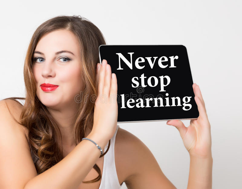 Never stop learning written on virtual screen. technology, internet and networking concept. beautiful woman with bare stock image
