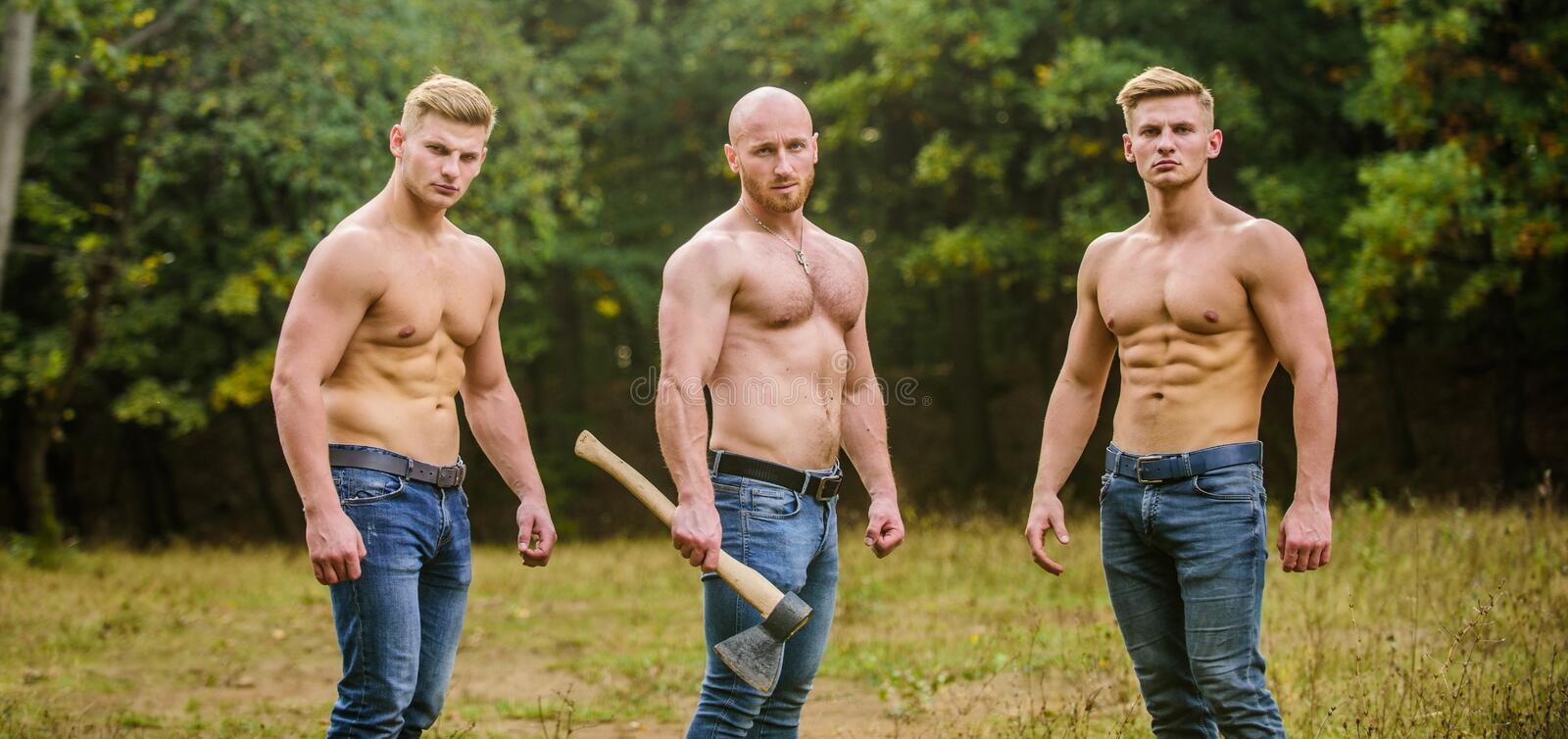 Never stop. Sports and leisure. mesomorph. three muscular men with axe. athletic man use ax. bodybuilders in jeans. Never stop. Sports and leisure. mesomorph stock photos