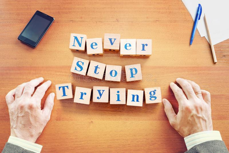 Never stop trying. Businessman made text from wooden cubes royalty free stock photos