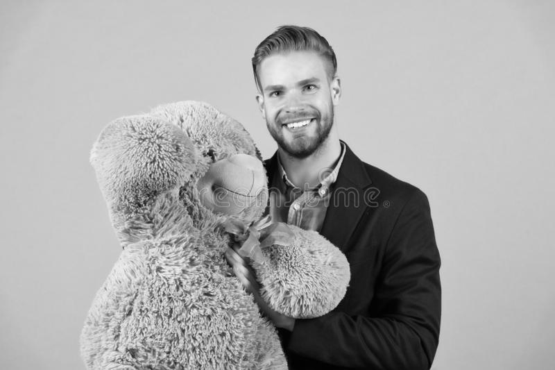 It is never too late to have happy adulthood. Man hols big teddy bear, grey background. Birthday gift concept. Teddy. Bear pleasant surprise. Guy happy hold stock photography