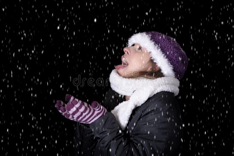 Nevicando sulla giovane donna in vestiti di inverno fotografie stock