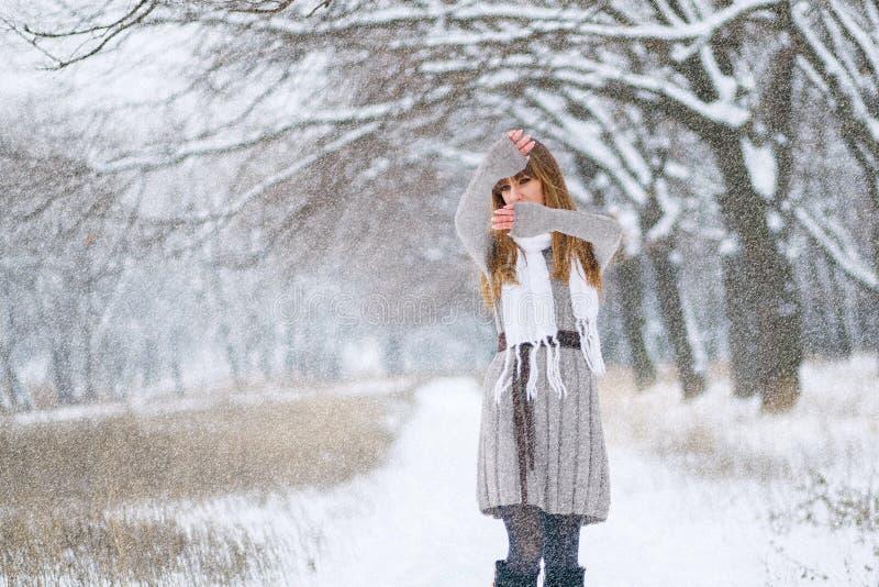 Nevicate invernali, una bella ragazza sola attraversa la neve fotografia stock