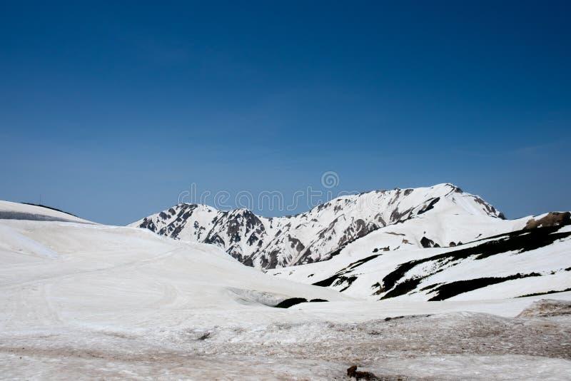 Nevichi sulle montagne e sulla vista del cielo blu alla stazione di Murodo dell'itinerario alpino di Tateyama Kurobe, alpi del Gi fotografia stock