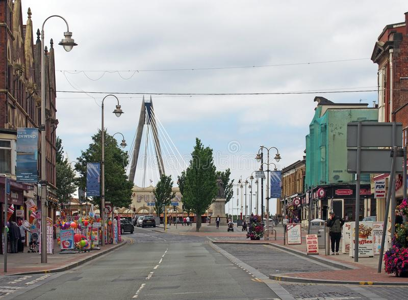 Nevill street ins southport with people walking past shops and pubs with the suspension bridge and amusement arcade at the end of. Southport, merseyside, united stock images