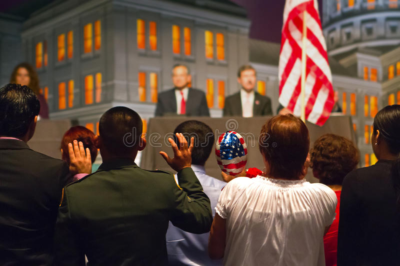 New American citizens. Immigrants swearing allegiance to the flag of the United States as part of a naturalization ceremony making them American citizens. The stock image