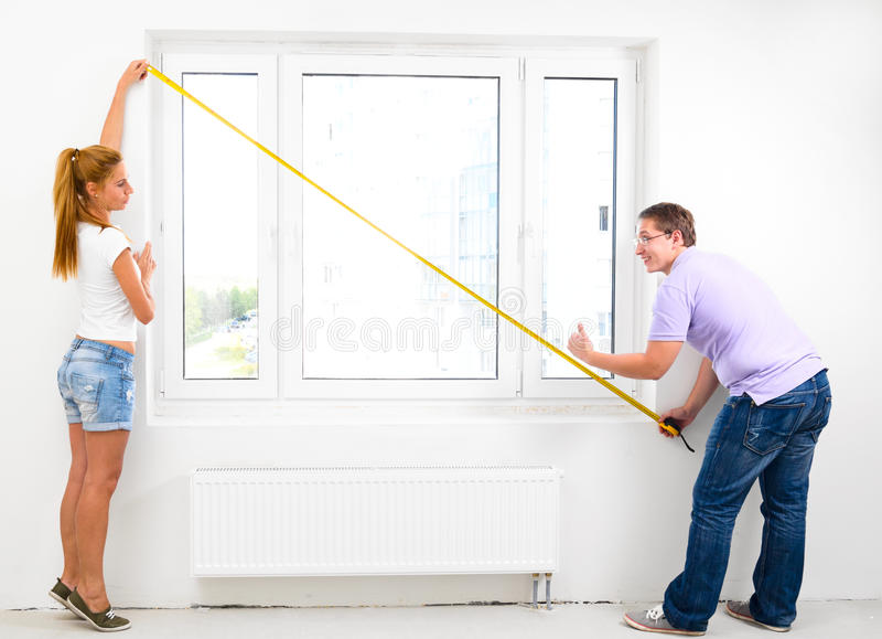 New apartment. Couple is measuring their new empty apartment stock photos