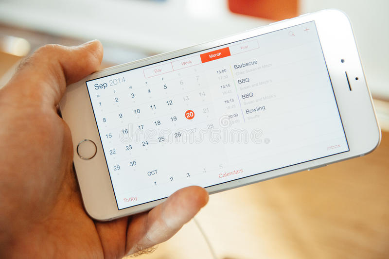 New Apple iPhone 6 and iPhone 6 plus calendar. PARIS, FRANCE - SEPTEMBER 20, 2014: Hand holding a iPhone 6 Plus displaying the new redesigned Calendar App during stock photography