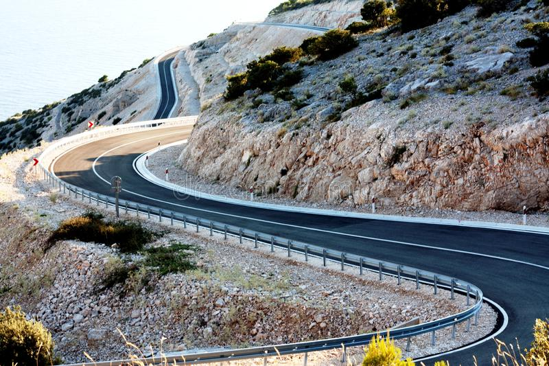 Asphalt road curving trough mountain royalty free stock photography