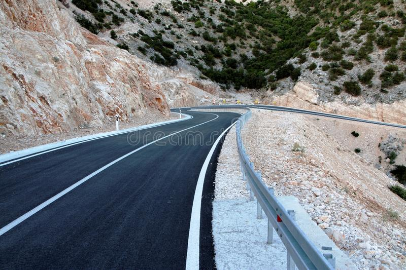 Asphalt road curving trough mountain stock images