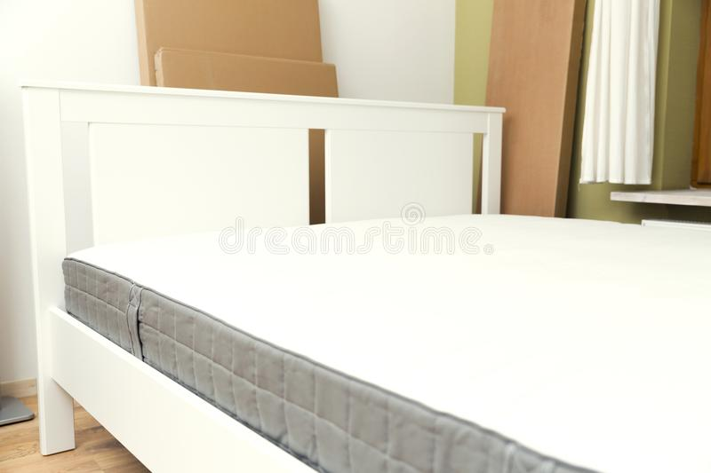 New assembled bed in the room with new mattress. Cardboard boxes on the background. furniture assembly royalty free stock photography