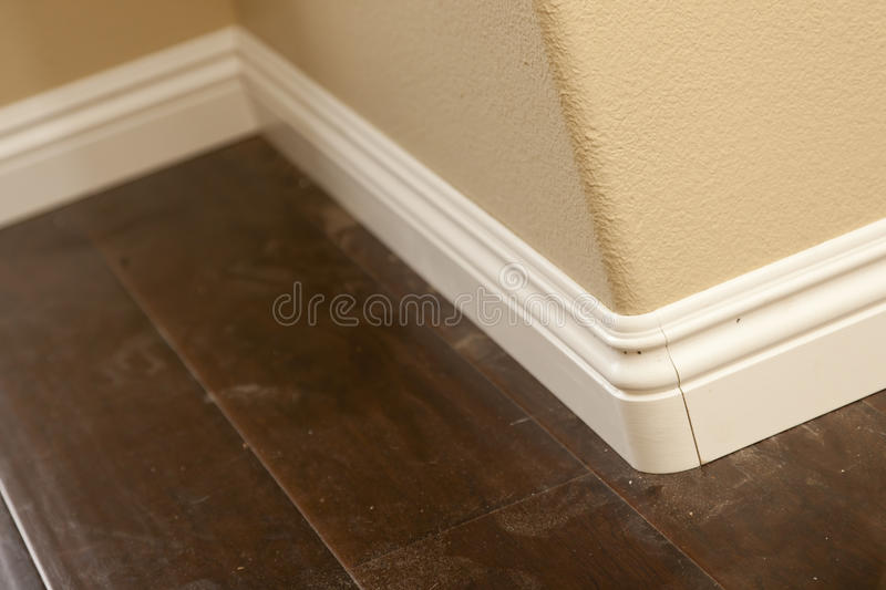 New Baseboard and Bull Nose Corners with Laminate Flooring. Abstract royalty free stock photography