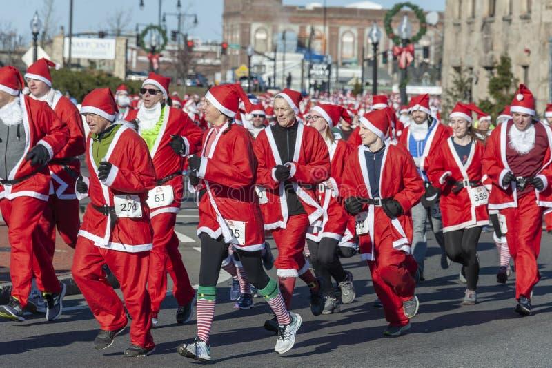 Santa hordes. New Bedford, Massachusetts, USA - December 8, 2018: Dense pack of costumed runners taking a corner during the Santa Sightings 5K Fun Run along royalty free stock photos
