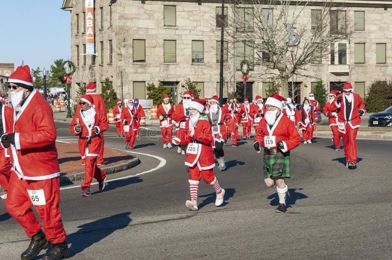 Santa Claus in kilt. New Bedford, Massachusetts, USA - December 8, 2018: Santa Claus in green plaid kilt amid pack of costumed runners taking a corner during royalty free stock image