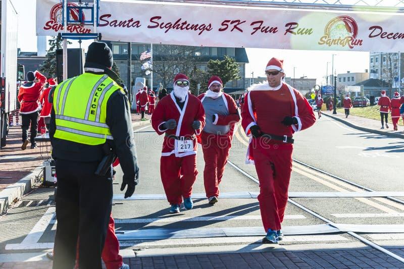 Three Santas finishing the Santa Sightings 5K. New Bedford, Massachusetts, USA - December 8, 2018: Three Santas finishing the Santa Sightings 5K Fun Run along royalty free stock images