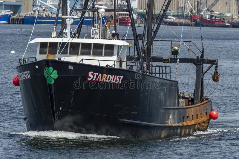 Commercial fishing boat Stardust going out on fishing trip. New Bedford, Massachusetts, USA - June 17, 2019: Commercial fishing vessel Stardust crossing New royalty free stock photo
