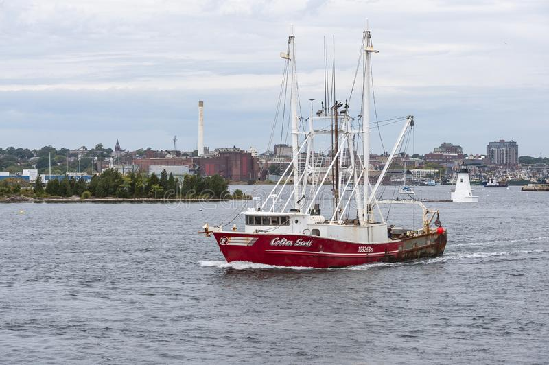 Scalloper Colten Scott passing lighthouse in New Bedford. New Bedford, Massachusetts, USA – October 2, 2019: Commercial fishing boat Colten Scott, hailing royalty free stock images