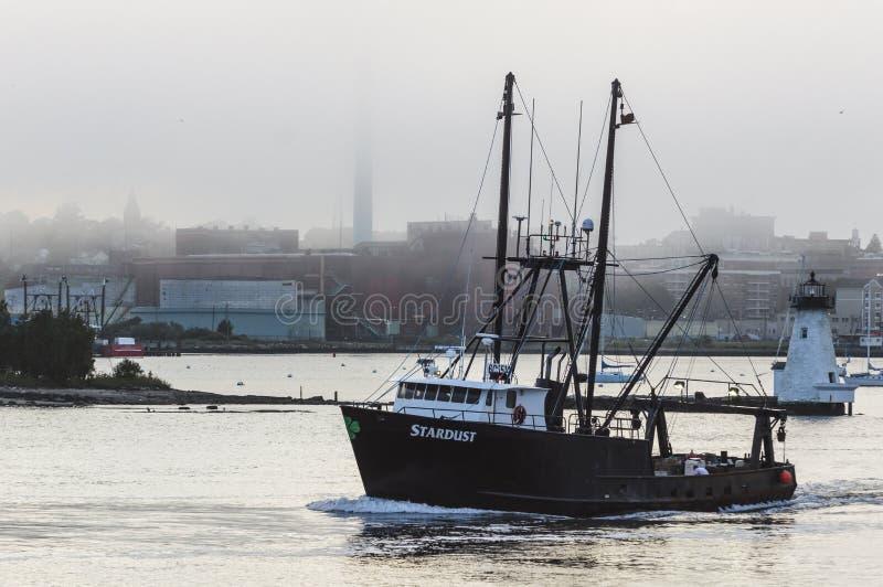 Commercial fishing vessel Stardust passing lighthouse. New Bedford, Massachusetts, USA - September 11, 2018: Commercial fishing vessel Stardust passing stock photography