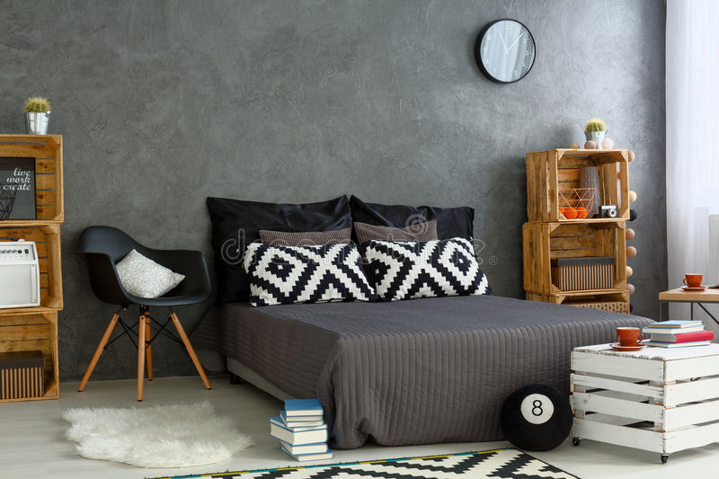 New bedroom with creative, DIY furniture. Spacious bedroom in grey, with handmade, wood furniture, big bed and decorative, pattern pillows stock photography