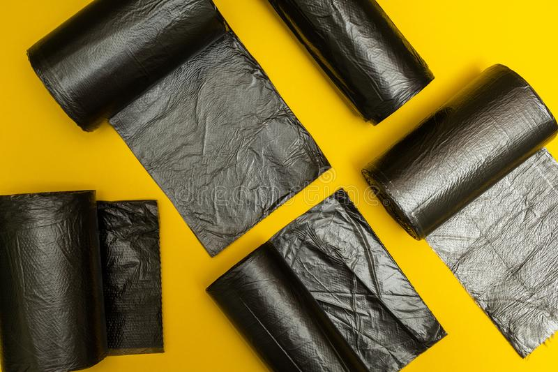 New black garbage bags on a yellow background.  stock photos