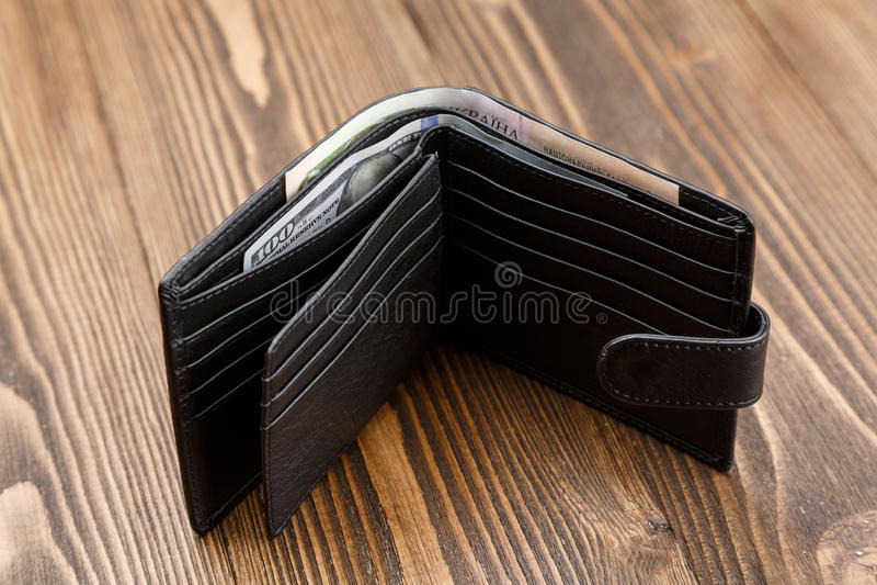 New black leather wallet over dark wooden background. New black leather wallet with money over dark wooden background stock photography