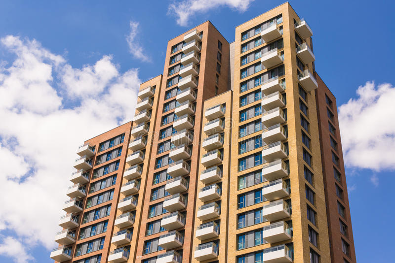 New block of modern apartments with balconies and blue sky. In the background stock images