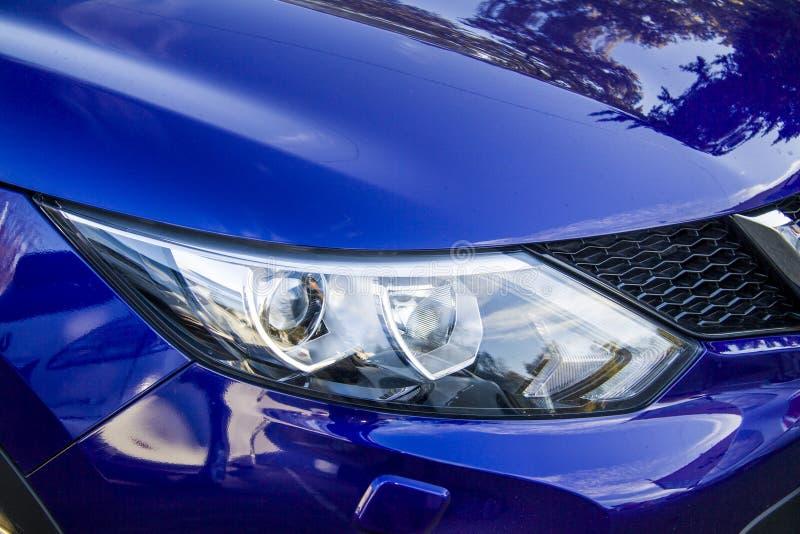 New blue car. New car in showroom, focus on xenon headlights stock photo