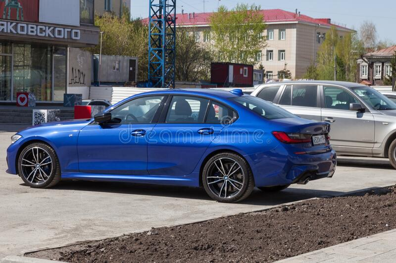 The new BMW 3 series car of a bright blue shiny metallic color against the backdrop of an urban Russian landscape. German. Novosibirsk, Russia - 04.26.2020: The royalty free stock image